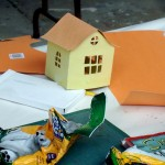 One student builds a house made out of construction paper and tape
