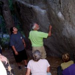 Daniel McCarthy (center) points out the rock climber's chalk marks on the rock that also houses a 300-500 year old rock painting