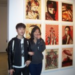 (from L) Kevin with classmate Cynthia, standing before Shepard Fairey's art