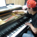 Nick reaches into the exposed piano keys to strum them