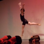 Andy leaps in the air over his fellow dancers